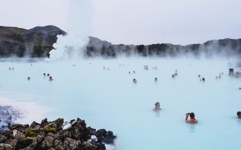 people swimming on hot spring near mountain during daytime
